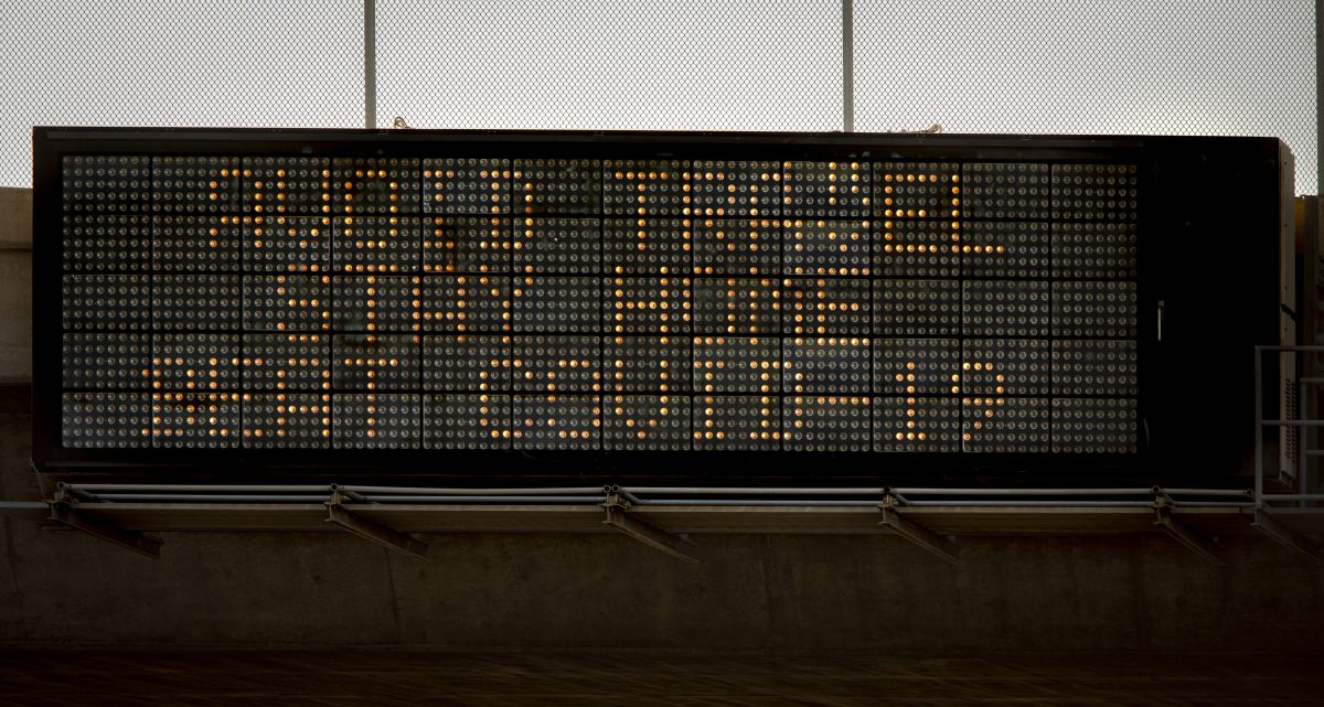 Freeway overpass sign stating Avoid Travel, Stay Home, Beat COVID-19